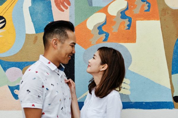 Eliza Sam and Joshua Ngo pose in front of a mural painting in Lisbon, as part of a Romantic photoshoot with Lisbon Photographers Your Story in Photos