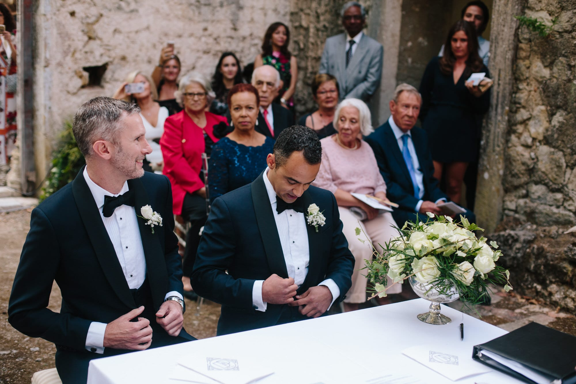 Two grooms take their seats at the ceremony on their wedding day