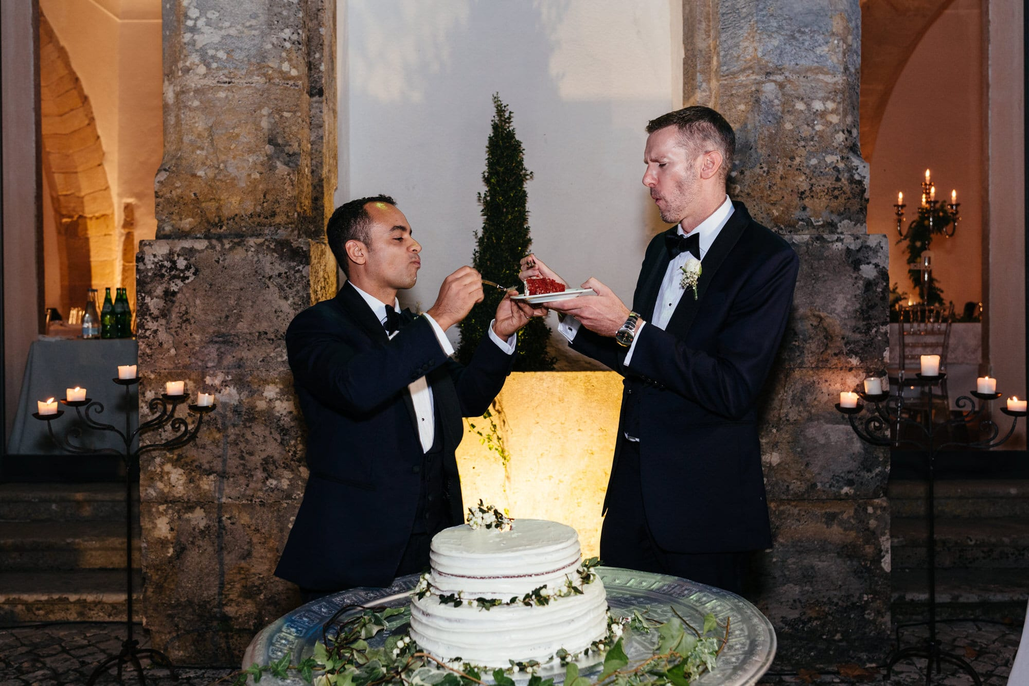 Grooms eating the wedding cake on their wedding day in Lisbon, Portugal